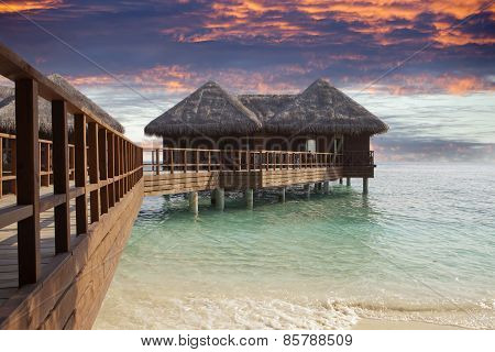 Lodges over water at the time sunset. Maldives.