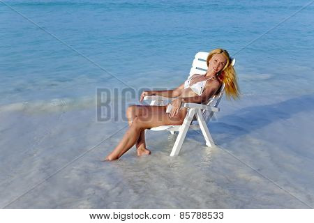 Young pretty woman in a beach chair in sea