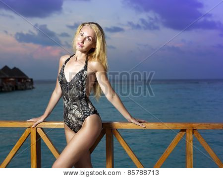 The attractive woman standing in a bathing suit against the evening sea. Maldives.