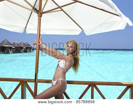 Young pretty woman stands in bathing suit on platform at villa on water Maldives