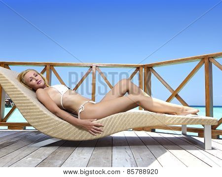 Young woman tans on a water villa terrace Maldives