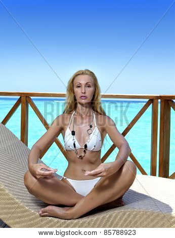 The young woman meditates on a sundeck of house over sea water Maldives