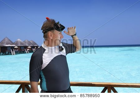 Young sports man with flippers mask and tube on sundeck of a house over the sea. Maldives