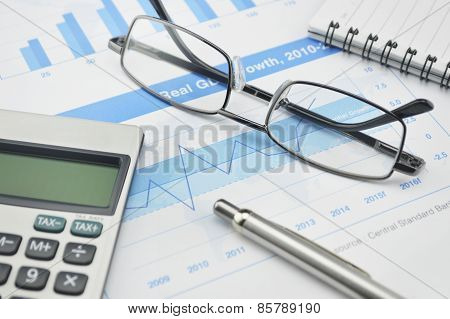 Glasses, Pen And Calculator On Financial Chart And Graph