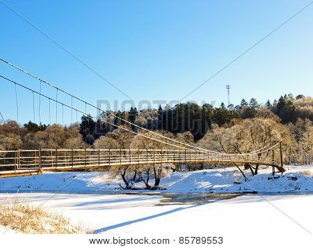 Suspension bridge across the river in winter