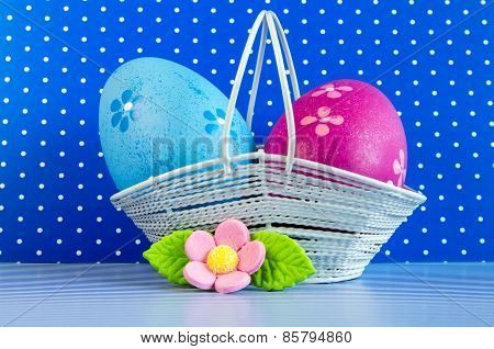 Blue And Crimson Easter Eggs In A Basket With Pink Flower
