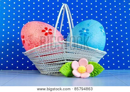 Pink And Blue Easter Eggs In A Basket With Pink Flower