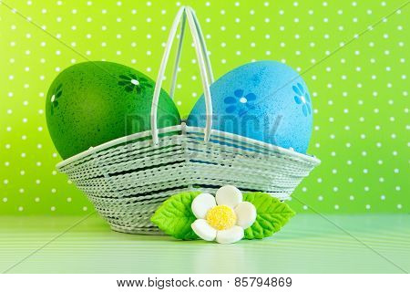 Green And Blue Easter Eggs In A Basket With White Flower