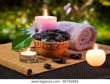 jar of black stones and candles on mat