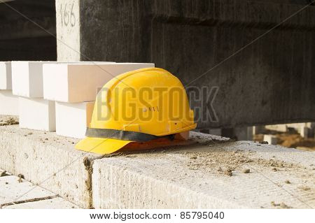 Construction yellow helmet lies on the wall of silicate blocks