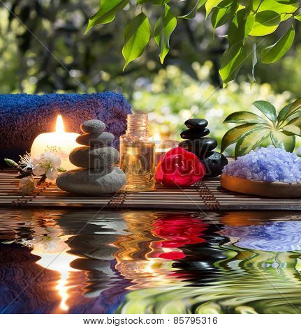 Candles , towels, stones and almond flowers in water