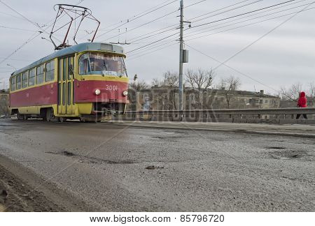 tram climbs onto the bridge. The road surface at the rail in need of repair