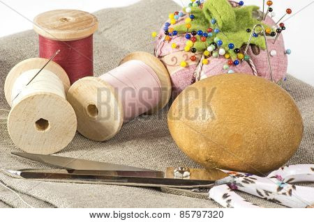 Threads, pin cushion and scissors