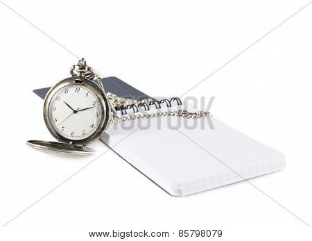 Pocket watch next to a note book