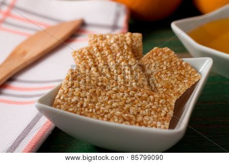 Sesame Wafers With Honey In White Bowl