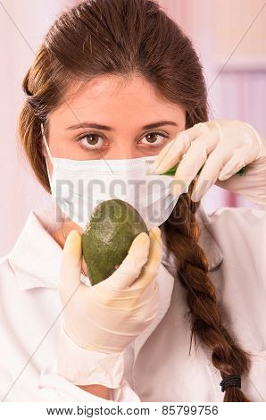 young beautiful woman biologist experimenting with avocado