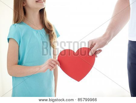 people, love, charity and family concept - close up of girl and male hand holding red heart shape at home