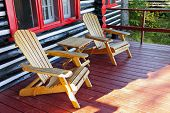 stock photo of log cabin  - Wooden log cabin cottage porch with adirondack chairs - JPG