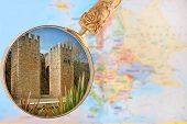 stock photo of lagos  - Looking in on Entrace into old town of Lagos Algarve Portugal with a magnifying glass or loop with European map in the background - JPG