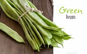 stock photo of phaseolus  - Piattoni green beans on the old wooden table - JPG