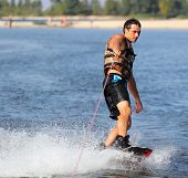 stock photo of watersports  - Wakeboarder in blackl shorts riding in sunset - JPG