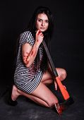 foto of bloody  - Young beautiful woman with a huge bloody axe over black background - JPG