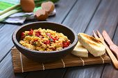 foto of scrambled eggs  - Scrambled eggs made with red bell pepper and green onion in rustic bowl with toasted bread on the side photographed with natural light  - JPG