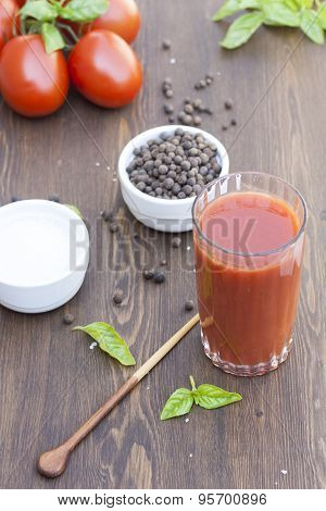 Tomato juice in glass with basil, spices and tomatoes cherry