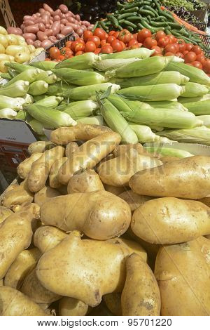 fresh potatoes and vegetables on a market stall