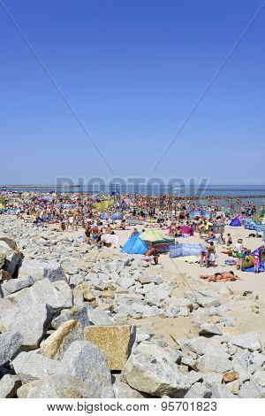 USTKA - JULY 04: Tourists enjoy the sunny weather and relaxing on the Baltic sea beach on 04 July 2015 in Ustka, Poland.