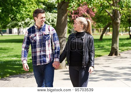 Affectionate Couple Strolling Through A Park