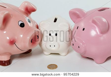 Three piggybanks on table with a coin closeup