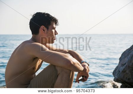 Handsome young man getting out of water with wet hai