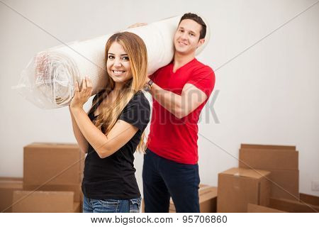 Cute Couple Carrying A Rug