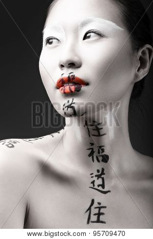 Beautiful Asian girl with white skin, red lips and hieroglyphics on her face. Art Beauty image.