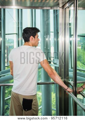 Handsome young man leaning against mirror inside an elevator or lift