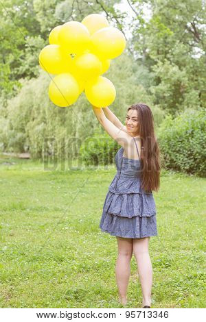 Attractive Young Woman With Yellow Balloons