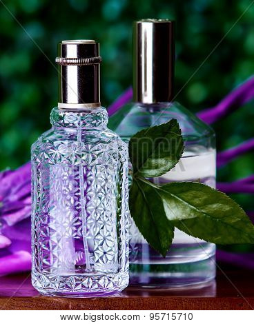 Two Perfumes On A Green Background