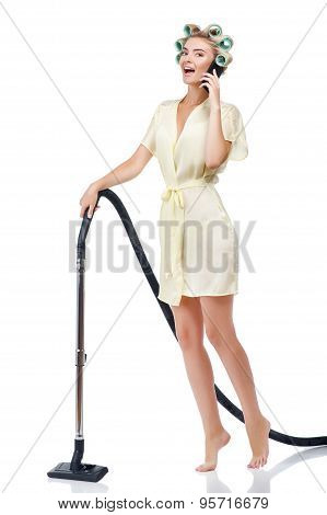 Beautiful young housewife with mobile phone is cleaning