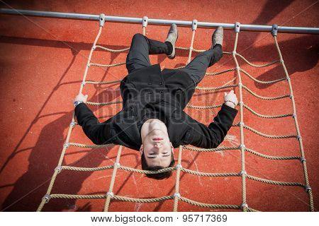 Full length shot of serious 20s man on climbling rope