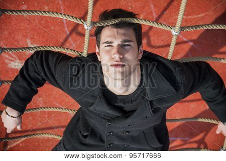 Full length of serious 20s man on climbling rope