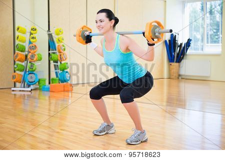Beautiful Sporty Woman Exercising With Barbell In Gym