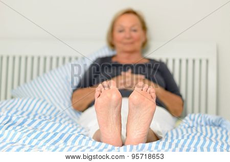 Bare Feet Of A Woman Relaxing In Bed