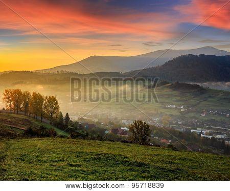 Meadow Near Village In Autumn Mountains At Sunrise
