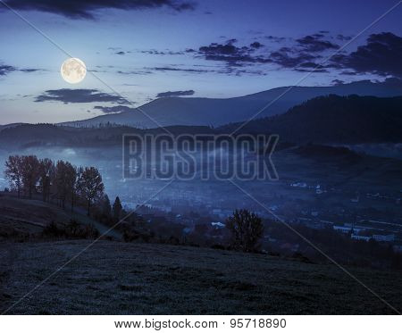 Meadow Near Village In Autumn Mountains At Night