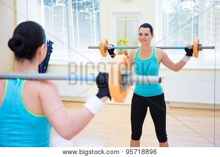 Bodybuilding Concept - Young Woman Exercising With Barbell