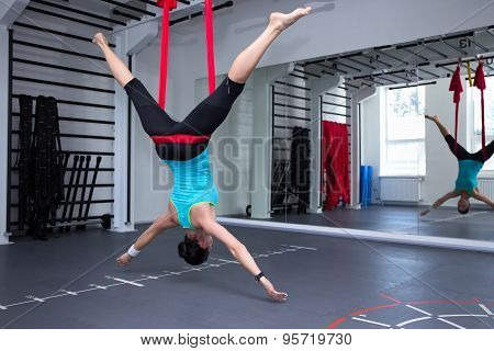 Young Woman Making Antigravity Yoga Exercises In Gym