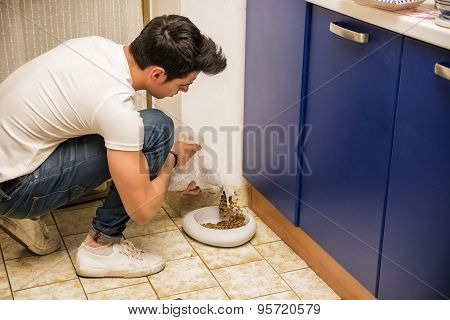 Young Man Filling Pet Bowl with Dry Food