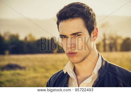 Handsome young man at countryside, in front of field or grassland