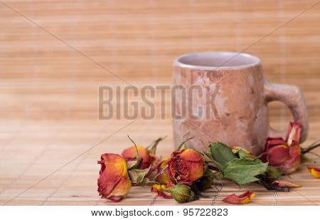vintage mag of roses tea and dry rosebuds on wooden background